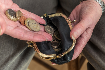 Pensioner counting money into her purse. British coins. Close up of hands. Poor pensioner concept. Stock Photo