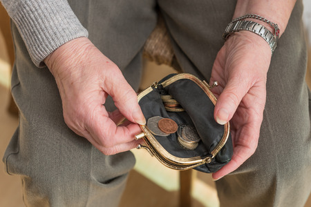 Hands of a pensioner checking her loose change in an open purse. British pounds sterling coins