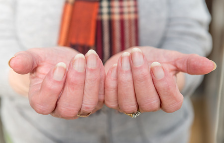 adentro y afuera: Close up of elderly ladys hands held out in front of her in a gesture of need.