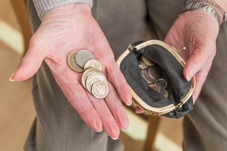 Hands of an elderly woman with British money in the palm of her hand and an open purse containing coins. Stock Photo