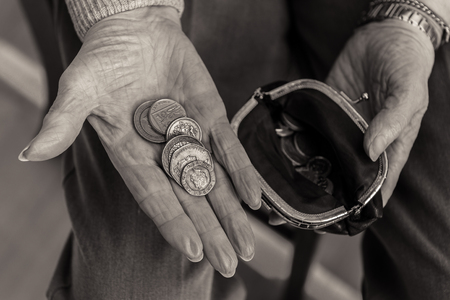 Money in the palm of a pensioners hand and open purse containing coins. British currency. Black and white image.