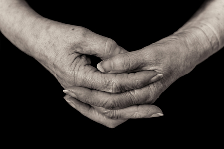 Close up of a female pensioners hands loosely clasped in a relaxed position on a black background. Monochrome.