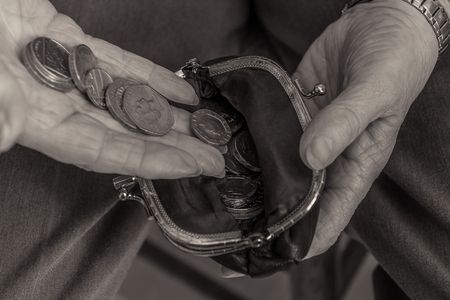 coppers: British pensioner putting coins into a purse. Close up of hands. Black and white image. Cost of living concept. Stock Photo