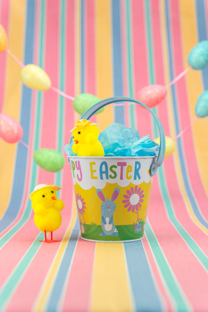 Pretty Easter fete scene with yellow chicks wearing hats and an enamel Easter decorated bucket. Vertical with copy space