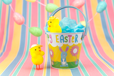 Easter chicks on a spring coloured striped background with egg garland and tin bucket.