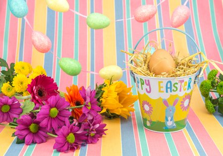 Colorful Easter display of vibrant fresh flowers, tin bucket, egg garland and candy striped background in beautiful spring colours.