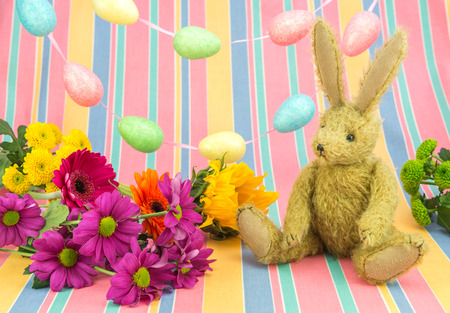 Happy Easter scene in spring colours. Vintage toy bunny rabbit with brightly colored fresh flowers, bucket, egg garland and candy striped background. Stock Photo