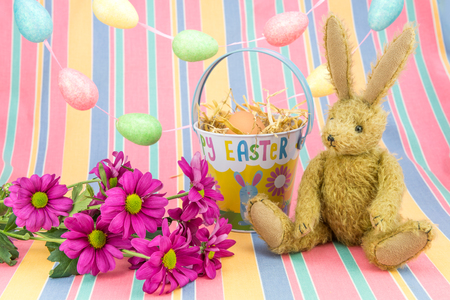 Happy Easter scene in spring colours. Vintage toy bunny rabbit with Chrysanthemum flowers, bucket, egg garland and candy striped background.