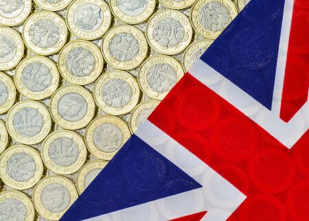 bimetallic: British money - new bimetallic one pound coins, introduced in March 2017 and Union Jack flag. Overhead point of view.