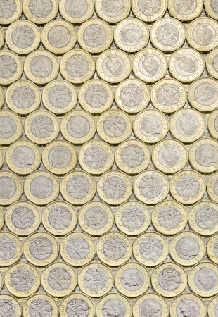 bimetallic: New pound coins background laid flat. Overhead point of view. The British bimetallic coin was introduced in March 2017.