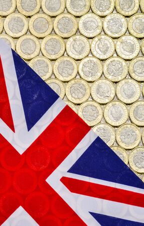 bimetallic: British Union Jack flag and currency - bimetallic one pound coins, introduced in March 2017. Overhead point of view. Vertical. Stock Photo