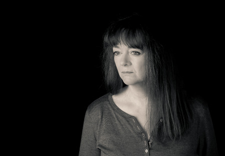 Black and white portrait of mature woman looking pensive. Low key. Copy space. Stock Photo