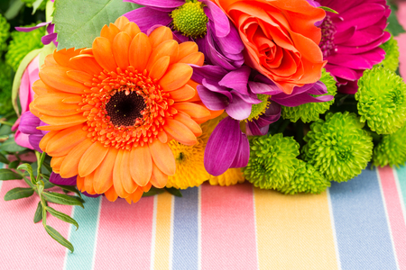 Orange Gerbera with fresh vibrant brightly coloured florist flowers on a pastel striped tablecloth. Copy space.