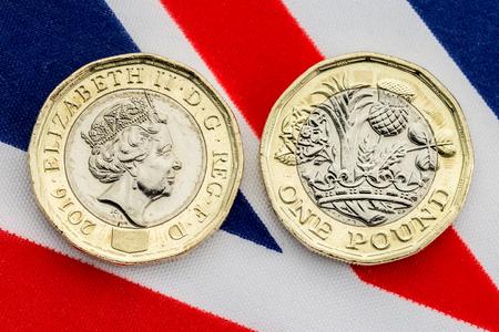 유니온 잭 플래그 배경에 머리와 꼬리를 보여주는 새로운 영국 파운드 동전. 2017 년 3 월에 도입 된 바이메탈 동전의 세부 사항을 닫습니다.