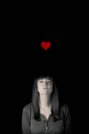 Portrait of a mature lady looking at a red heart drifting away. Elusive love concept. Minimal, low key, vertical and with copy space. 2 of 3.