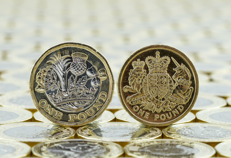 bimetallic: Comparison of new and old British one pound coins showing the back or tails side. On a background of money. The new British one pound coins were introduced in 2017. Stock Photo