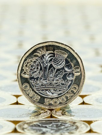 Macro detail of British one pound coin. Rear view, tails side on a background of one pound coins. The new British one pound coins were introduced in 2017
