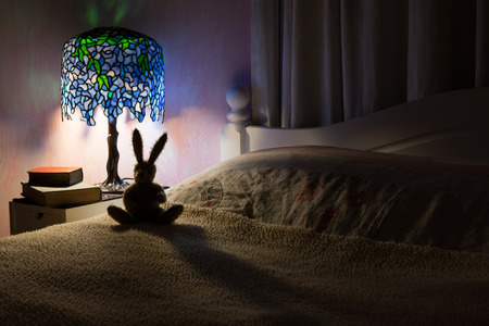 Bedroom interior at night. A dark room illuminated by a Tiffany style lamp silhouetting a toy rabbit.  Story time at bedtime concept.