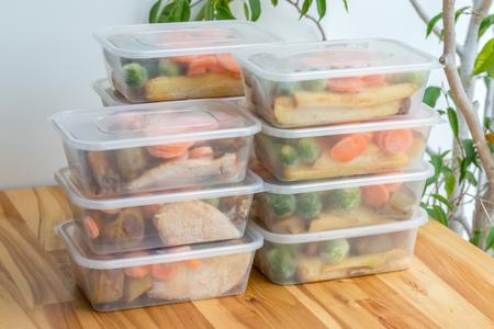 Preparación de comidas Pila de cenas caseras de pollo asado en recipientes listos para ser congelados para su uso posterior.