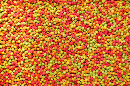 Background overhead image of colourful pet food pellets for parrots. Highly dyed in pink, orange, yellow and green colours.