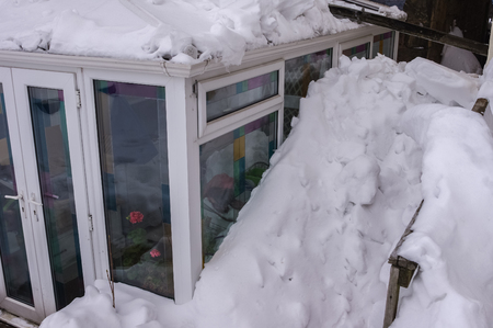 Snow piled high at side of a conservatory after a bad snow storm having slid off the main roof.