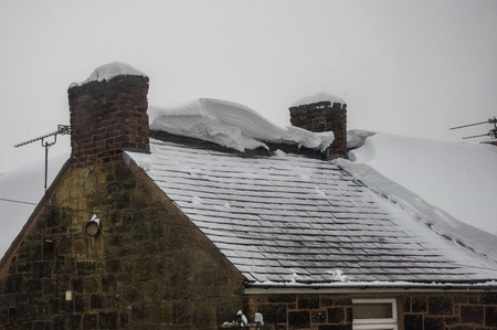 Thick snow on house roof has slid off leaving exposed slate roof tiles and broken edges of the remaining snow. Sandstone building circa 1800 in Wales UK.