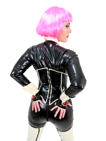 Attractive woman in black latex rubber catsuit and corset costume with short hair pink wig. Back view with hands on buttocks. Profile of face. White background.