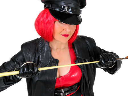 Dominant woman wearing latex and leather, red and black military clothes including gloves, cap and coat. In a short red wig and holding a whip. Fetish cosplay. White background.