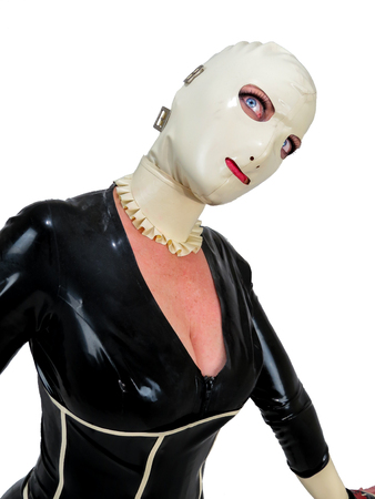 Freaky hooded cosplay woman in black latex rubber catsuit and cream hood. Big blue staring eyes. Creepy doll fetish costume. Portrait with white background. Banque d'images