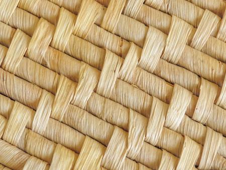 Sluit omhoog van natuurlijke geweven mat die detail van het geweven patroon toont. Gedroogde bladeren worden gebruikt om het ontwerp te maken. Achtergrond textuur.