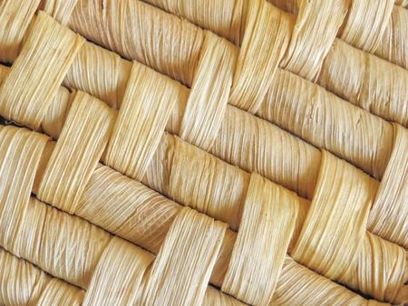 Macro dichte omhooggaand van natuurlijke geweven mandenmakerij die detail van het geweven patroon toont. Gedroogde bladeren worden gebruikt om het ontwerp te maken. Achtergrond textuur.