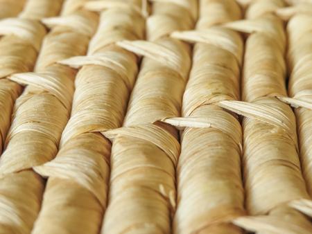 Sluit omhoog rijen van natuurlijke geweven mandenmakerij die detail van het geweven patroon toont. Gedroogde bladeren worden gebruikt om het ontwerp te maken. Achtergrond textuur. Stockfoto
