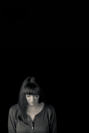 Minimal portrait of mid aged woman with problems looking down. Vertical low key monotone with lots of copy space.
