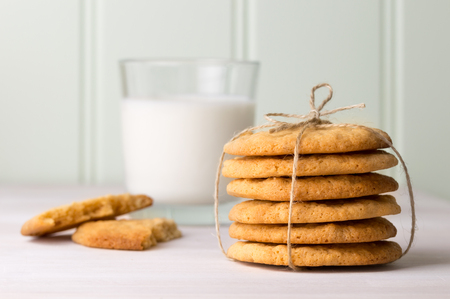 Kids snack. Peanut butter cookies and glass of milk. Stack of the homemade golden biscuits tied with twine. In a kitchen setting.