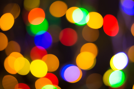 Bright party lights, multi-colored defocussed bokeh background. Blurred Christmas fairy lights. Close up. Stock Photo