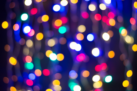 Bokeh lights background, curtain of Christmas fairy lights. Abstract holiday lights defocused.