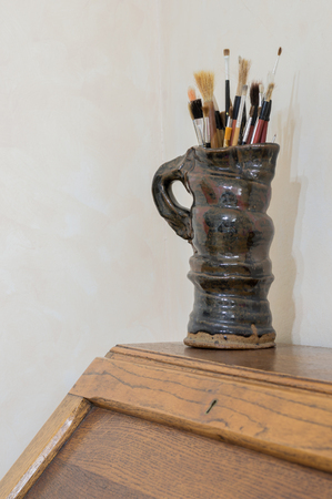 Collection of artists paintbrushes in a handmade glazed pottery jug. On a wooden table with cream background in an authentic artists studio. Vertical with copyspace.