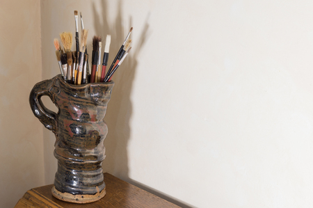 Collection of artists paintbrushes in a handmade glazed pottery jug with strong shadow. On a wooden table with cream background in an authentic artists studio. Copy space, Stock Photo