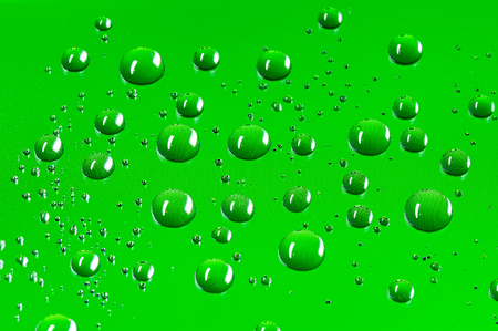 Round water droplets background with a pattern of pixels in a bright green colour.