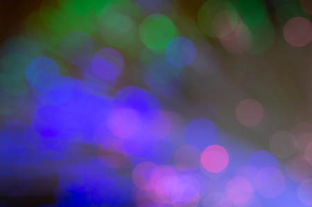 Defocused fiber optics with green, blue and pink bokeh. Close up abstract with dark background.