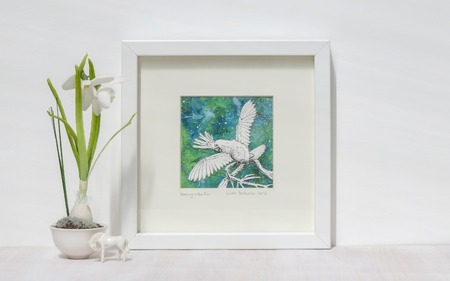 White interior display. Framed mixed media collage of Cockatoo parrot with wings outstretched. Snowdrop flower and horse ornament.