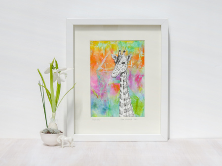 White interior setting. Framed mixed media collage of giraffe with rainbow coloured background. Snowdrop flower and horse ornament. Stock Photo