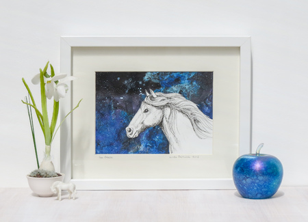 White interior display. Drawing of horses head on a collaged blue background in frame. With iridescent blue glass apple and snowdrop on a shelf.