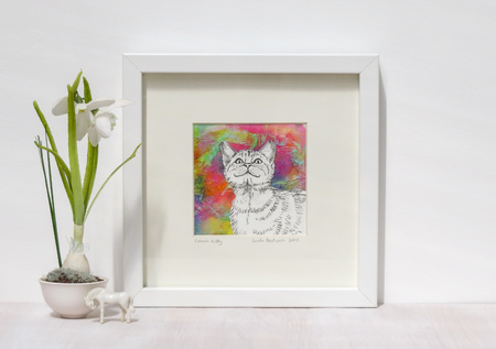 White interior display. Drawing of smiling cat on a vibtant colourful collaged background in a frame. With a snowdrop on a shelf. Stock Photo