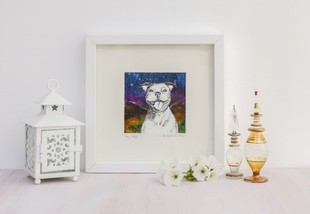 White interior display. Drawing of a happy Staffy dog with a big smile, on a collaged background in frame. With egyptian glass scent bottles, tea light and cherry blossom. Stock Photo