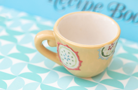 Yellow decorated measuring cup in a teacup shape on a blue retro patterned background with blurred recipe book writing on an angle.
