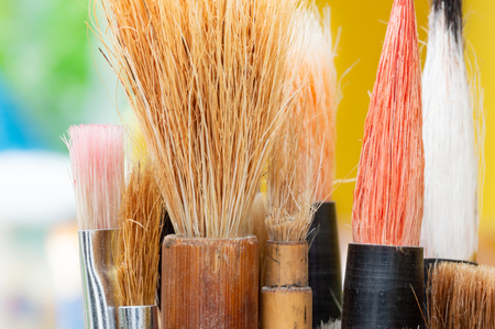Artists paint brushes with yellow and green background. Close up detail of the bristles. Mostly chinese watercolour brushes.