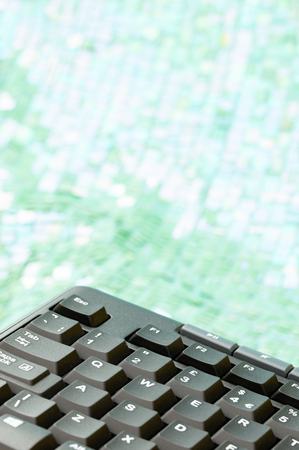 Part of black computer keyboard with mint green and white bokeh background. Copy space. Vertical. Stock Photo