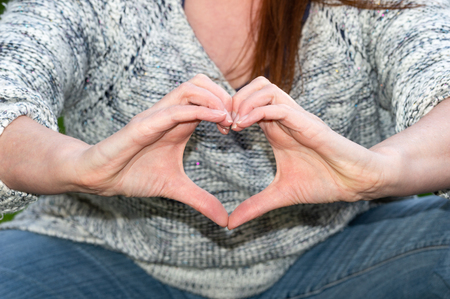 Woman in casual clothes making heart shape with hands in front of her body. Authentic style.