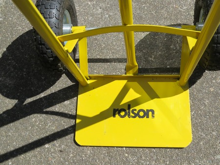 WREXHAM, UK - AUGUST 27, 2015: Heavy duty empty yellow Rolston sack barrow with shadows viewed from above. Close up.